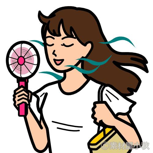 手持ち扇風機で涼し気な若い女性